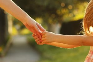 A mother lovingly holding a childs hand