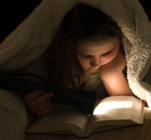 A young girl under the blankets with a flashlight and a book