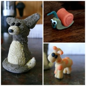 a cat, snail and giraffe made from clay